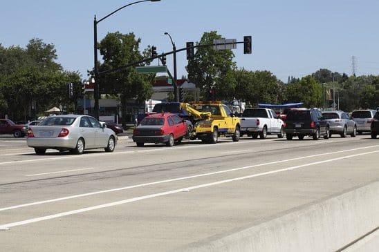 Yellow Tow Truck Hauling Car In Traffic