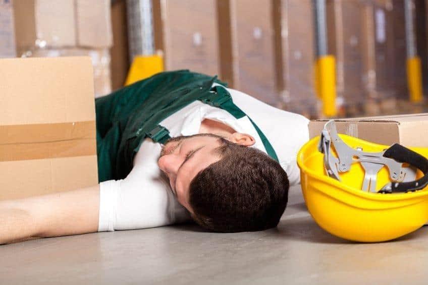 warehouse employee lying on the floor with hard hat