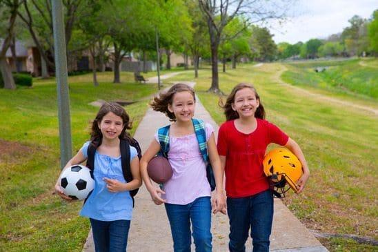 Children kid girls walking to schoool with sport balls