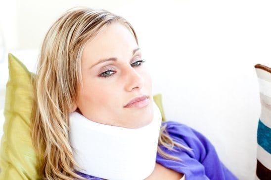 Beautiful woman wearing neckbrace lying on a sofa