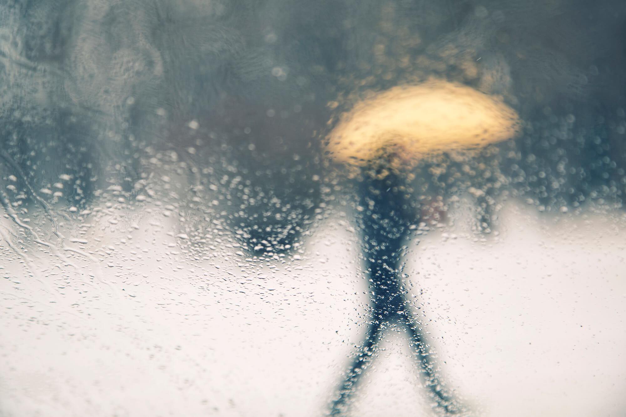 pedestrian walking in the rain with umbrella