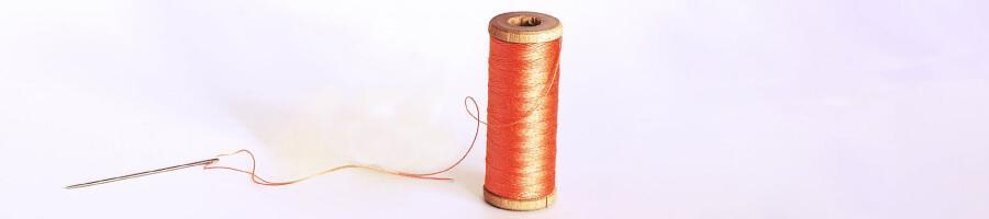 orange thread and threaded needle on white background