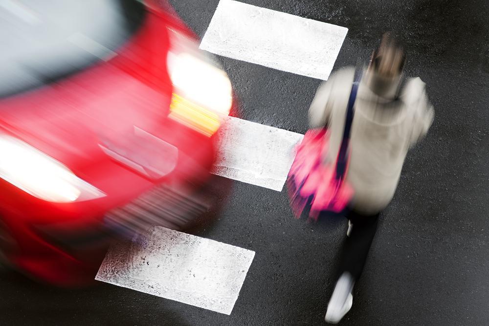 Blonde woman walking in a crosswalk with a red car speeding toward her.