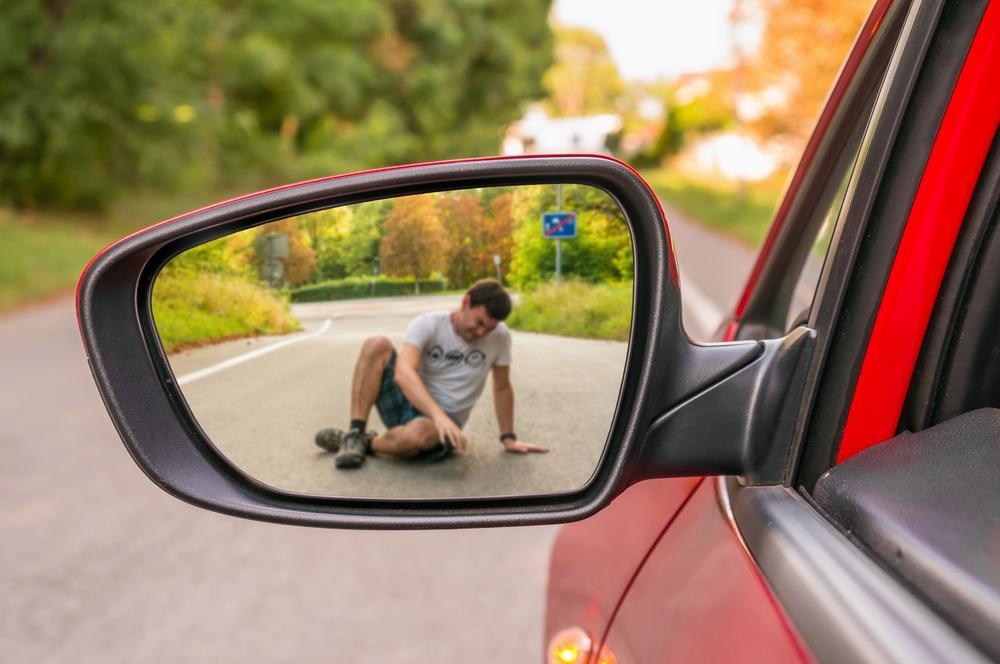 man lying in road in rearview mirror