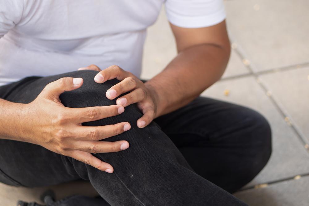 man on floor clutching knee
