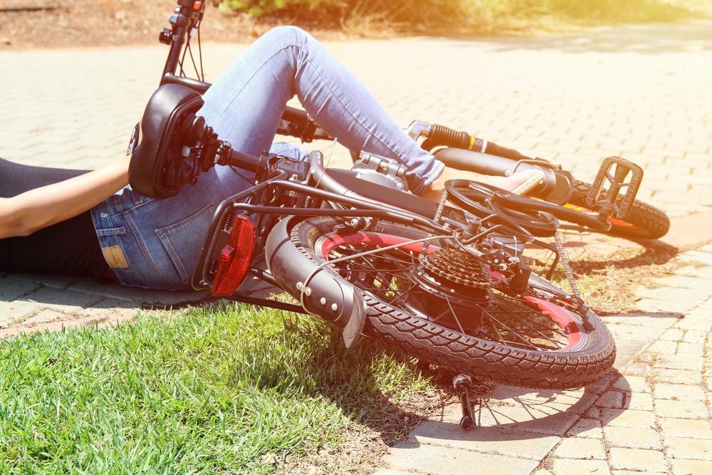 Woman on bike laying down on grass next to a brick sidewalk