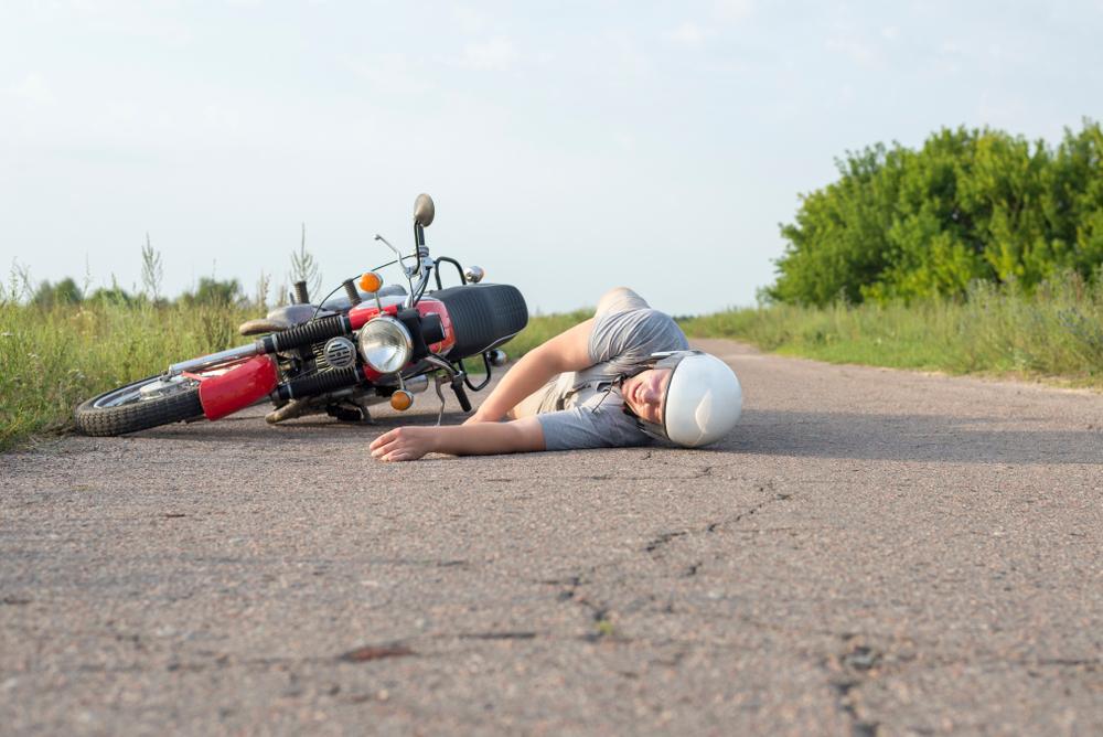 a man lying on the asphalt near his motorcycle