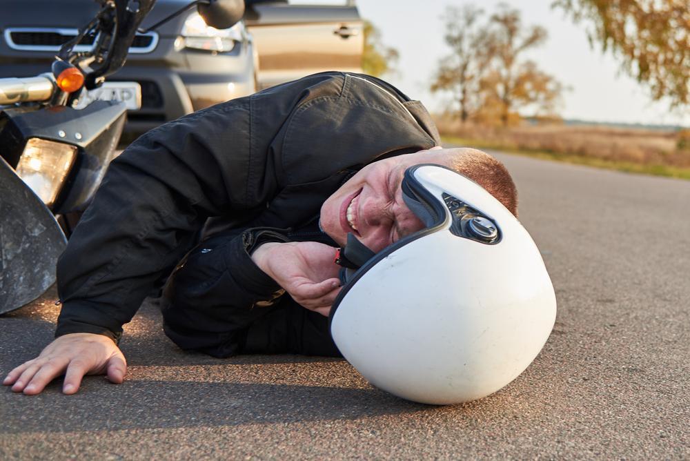 injured motorcyclist on asphalt near his crashed bike
