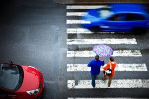 pedestrian crosses street while car drives through crosswalk