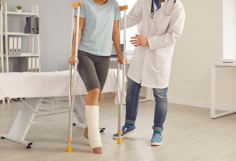 doctor helps patient with broken leg