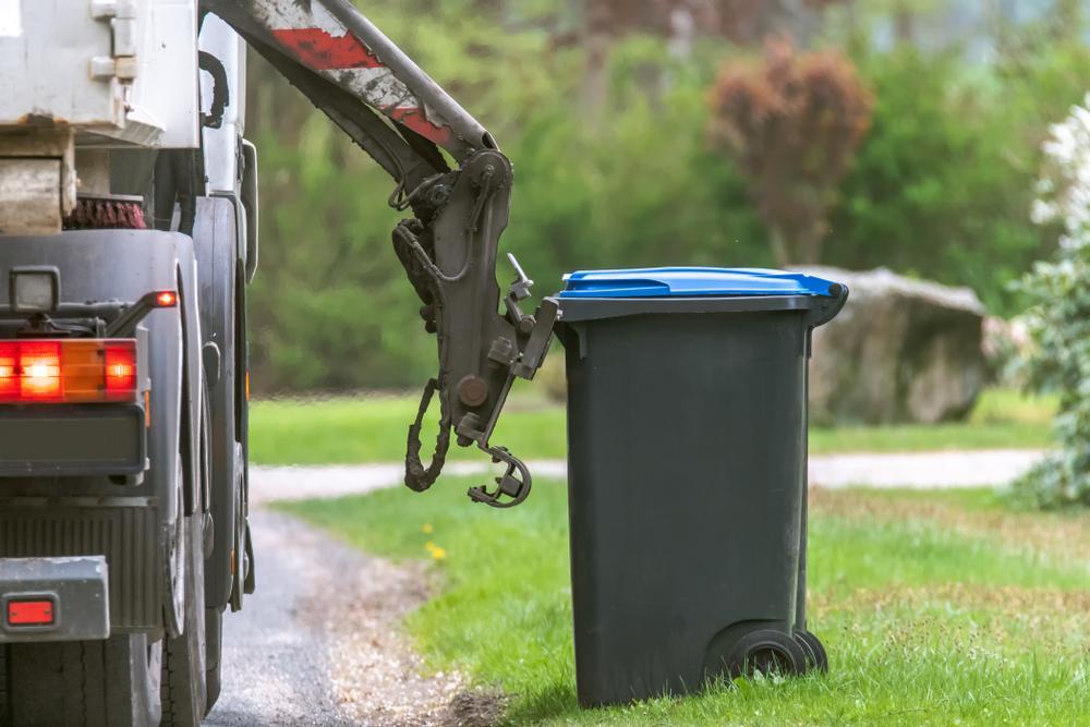 garbage truck picks up trash bin