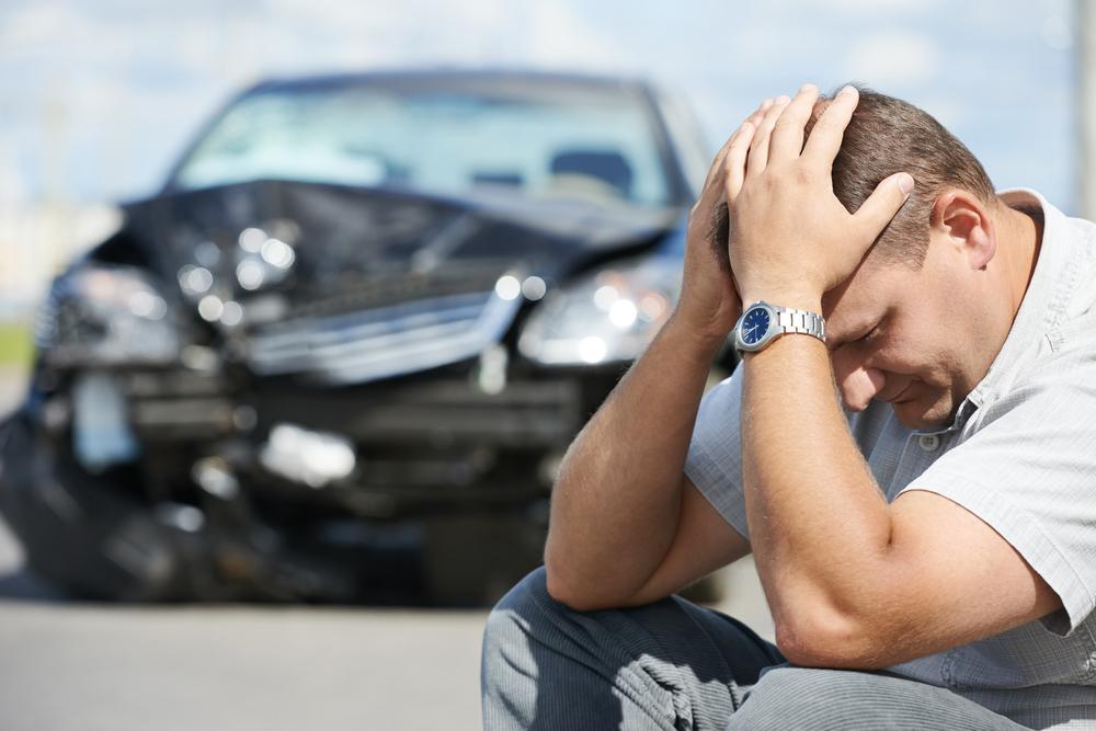 upset driver sits near his damaged vehicle