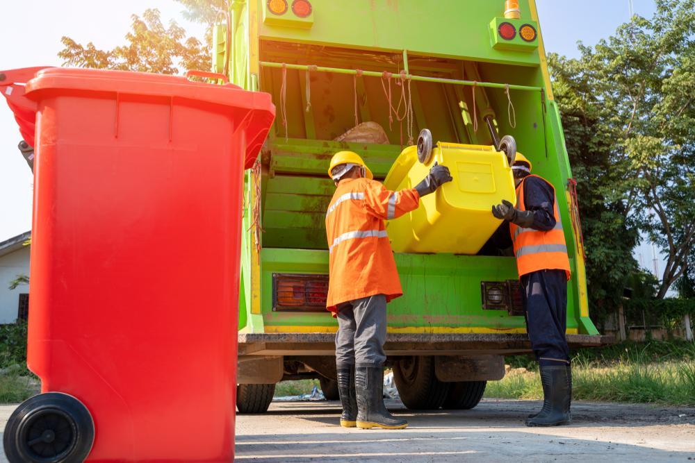 sanitation workers load garbage truck