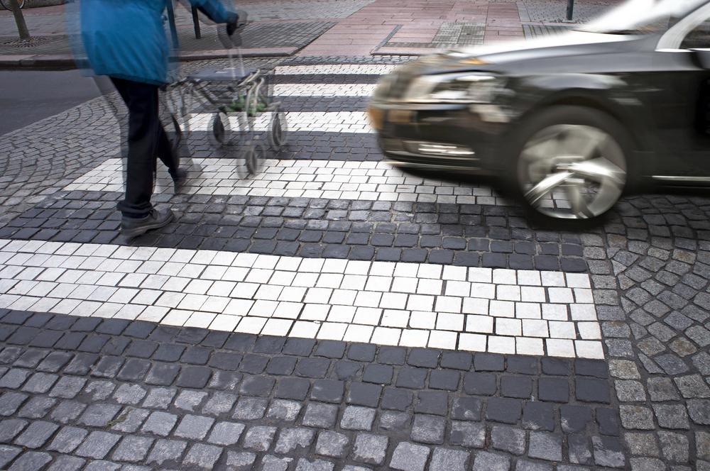 speeding car approaches crosswalk with senior pedestrian