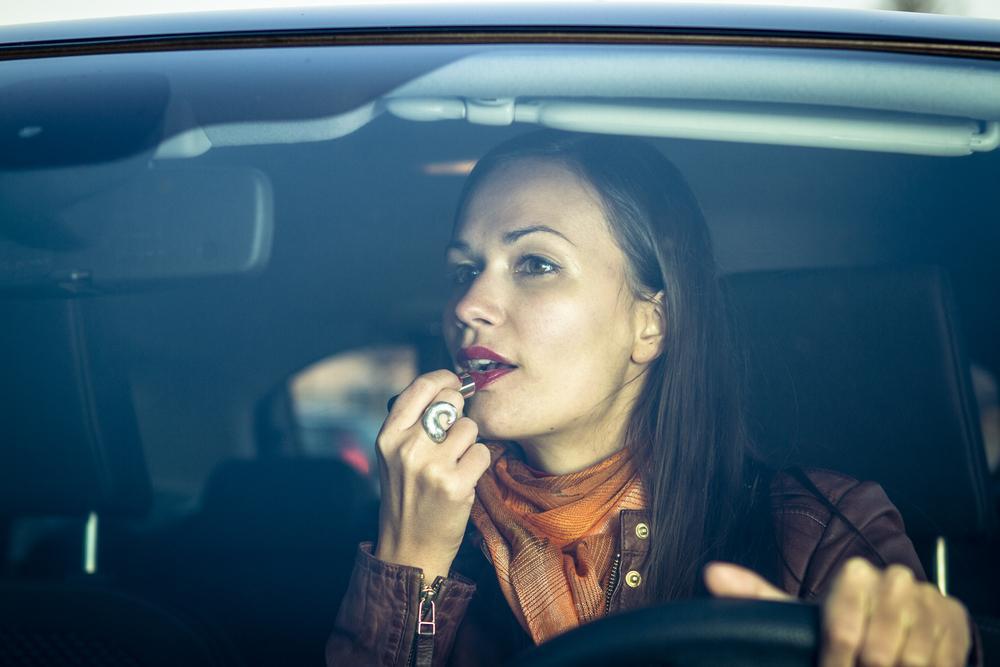 woman applies makeup while driving