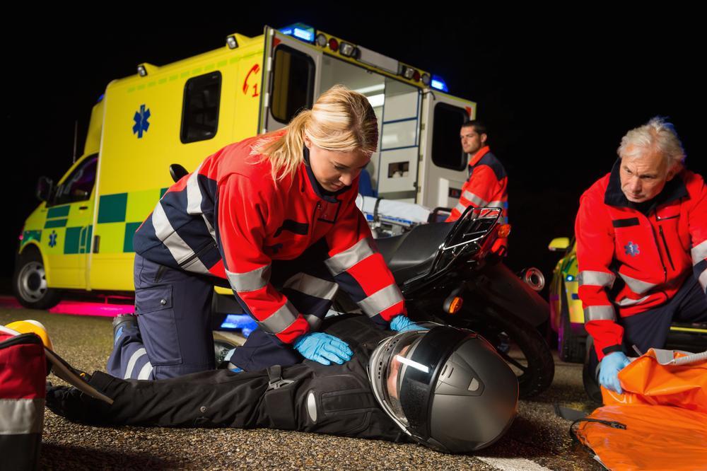 paramedics assist injured motorcyclist after accident